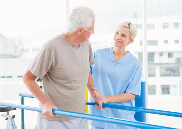 senior man walking assisted by his caregiver